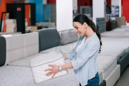 smiling woman with folding mattress in hands in furniture shop