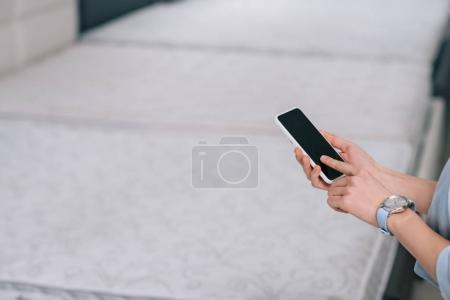 partial view of woman using smartphone with blank screen in furniture store
