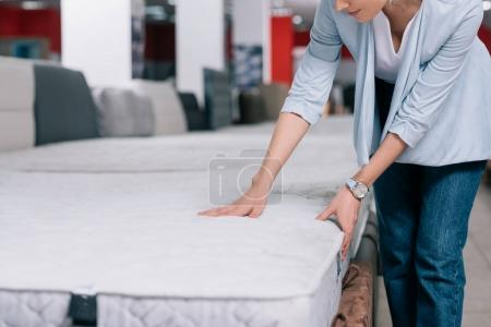 Photo for Partial view of woman touching orthopedic mattress in furniture shop - Royalty Free Image