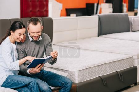 smiling couple with notebook sitting on mattress in furniture store
