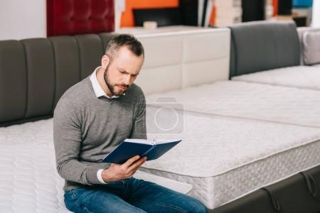 focused man reading notes in notebook in furniture shop with arranged orthopedic mattresses