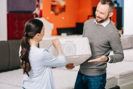 couple choosing folding mattress together in furniture store with arranged mattresses