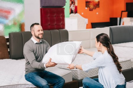 Photo for Smiling couple with pillow in furniture store with arranged mattresses - Royalty Free Image
