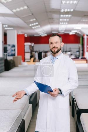 shop assistant with notepad pointing at orthopedic mattresses in white coat in furniture shop
