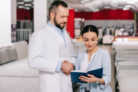 male shop assistant in white coat and woman with notebook in furniture shop with arranged mattresses behind