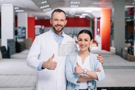 Photo pour Portrait de client souriant et assistant de magasin masculin montrant pouces vers le haut dans le magasin de meubles - image libre de droit