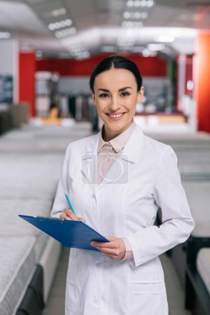 selective focus of smiling shop assistant in white coat with notepad in furniture shop with arranged mattresses