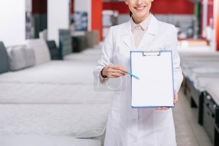 Photo for Cropped shot of smiling shop assistant in white coat pointing at empty notepad in hand in furniture shop with arranged mattresses - Royalty Free Image
