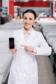 smiling shop assistant in white coat showing smartphone with blank screen in hand in furniture shop with mattresses