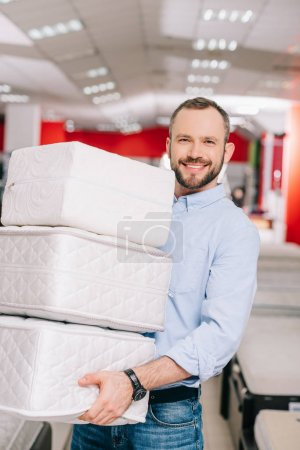 smiling man holding pile of folding mattresses in hands in furniture store
