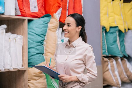 smiling shop assistant with notepad looking at arranged pillows in furniture shop