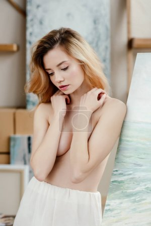 sensual naked artist standing near easel and looking down in art studio