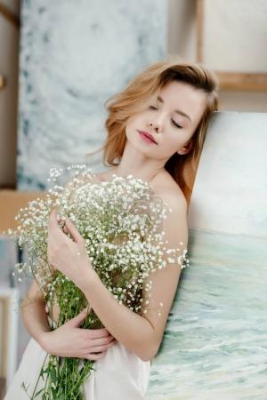 sensual naked girl with closed eyes holding white flowers and leaning at easel in art studio