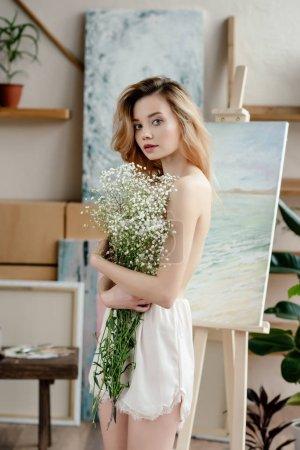 Photo pour Belle jeune femme nue tenant des fleurs blanches et de regarder la caméra en studio d'art - image libre de droit