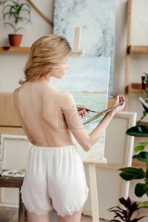 Photo pour Vue arrière du nue jeune femme tenant palette et photo de peinture dans l'atelier d'art - image libre de droit