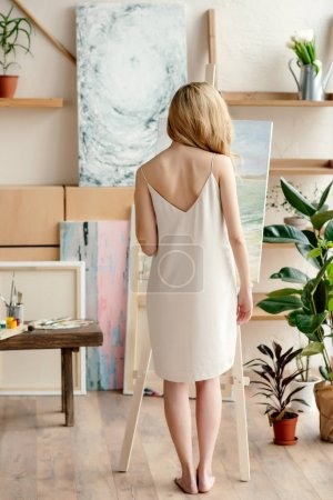 back view of tender young barefoot woman standing near easel in art studio