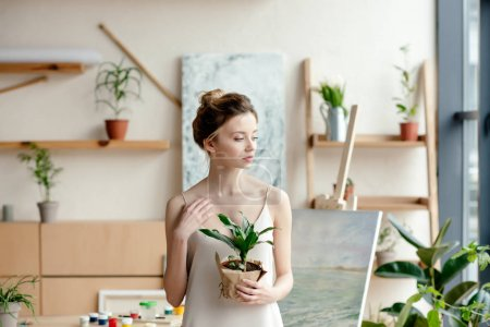 beautiful tender female artist holding potted plant and looking away in art studio