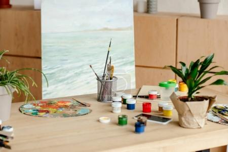 Photo pour Vue rapprochée du lieu de travail de l'artiste avec pinceaux et palette dans le studio d'art - image libre de droit