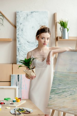 beautiful tender girl holding potted plant and leaning at easel in art studio