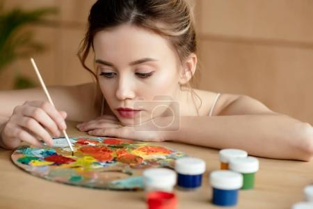 Photo for Beautiful young artist holding brush and looking at palette in art studio - Royalty Free Image