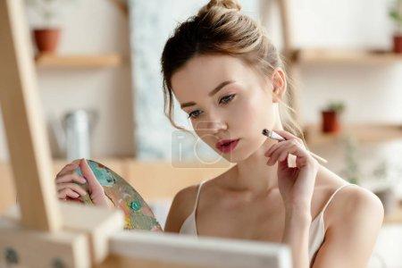 Photo pour Attrayant fille avec pinceau et palette tableau de peinture dans le studio d'art - image libre de droit