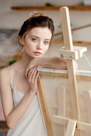 beautiful young woman leaning at picture on easel and looking at camera in art studio