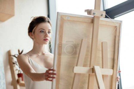 Photo pour Belle jeune artiste regardant l'image sur chevalet - image libre de droit