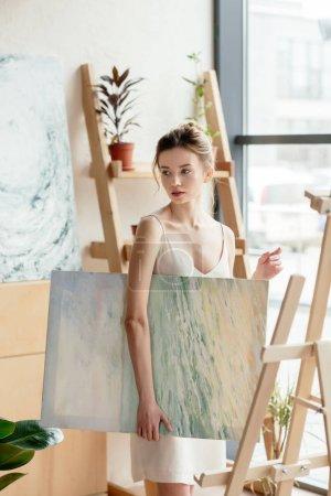 Foto de Hermosa joven sosteniendo la imagen y mirar lejos en el estudio de arte - Imagen libre de derechos
