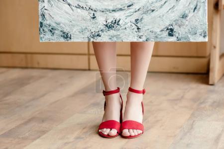 Photo pour Plan recadré de jeune artiste féminine en sandales rouges tenant photo - image libre de droit