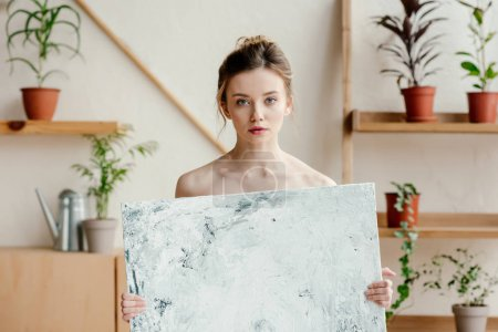 beautiful young naked artist holding picture and looking at camera
