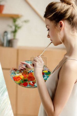 side view of attractive young artist with palette and brush painting on easel in studio