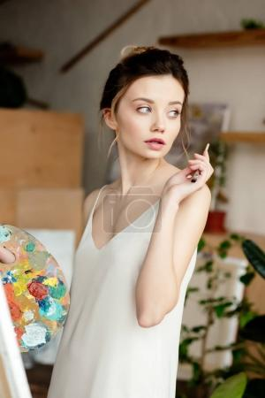 beautiful young artist holding palette and looking away in studio