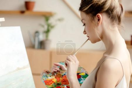 Photo for Side view of attractive female painter holding palette and brush in art studio - Royalty Free Image