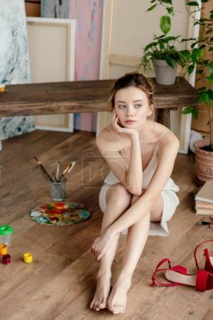 Photo pour Belle jeune artiste cher assis sur le sol et regardant loin dans l'atelier d'art - image libre de droit