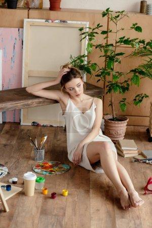 Photo pour Belle tendre pieds nus fille assise sur le sol et regardant loin dans le studio d'art - image libre de droit