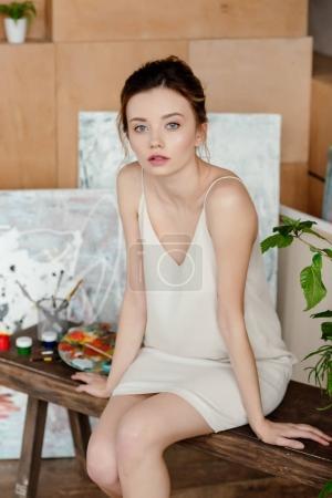 Photo pour Belle jeune peintre féminine regardant la caméra alors qu'elle était assise dans un studio d'art - image libre de droit