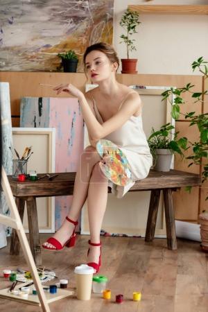 Photo pour Belle jeune artiste tenant la palette et assis en studio - image libre de droit