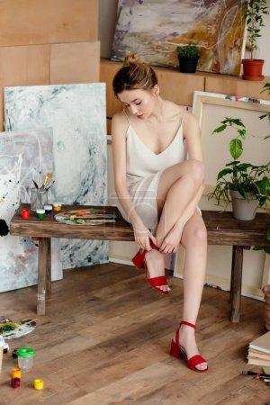 Photo pour Belle jeune femme tendre portant des sandales rouges dans le studio d'art - image libre de droit