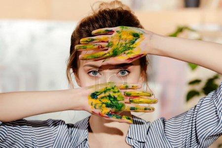 Photo pour Belle jeune artiste avec des paumes en peinture regardant la caméra - image libre de droit