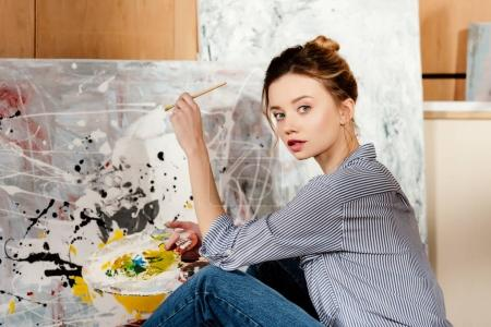 beautiful young artist holding palette and looking at camera in art studio
