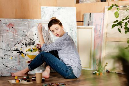 Photo pour Belle jeune artiste pieds nus assis sur le sol et peinture tableau en studio - image libre de droit