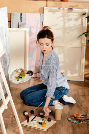 beautiful girl holding palette and painting in art studio