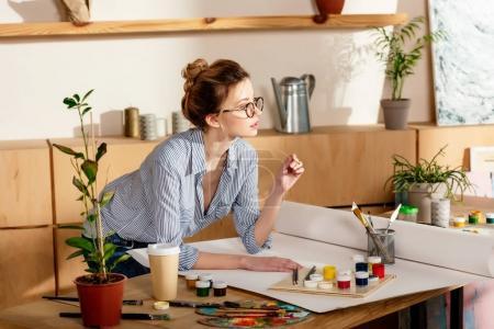 Photo pour Jeune artiste féminine en lunettes permanent à table avec toile vide et la peinture fournitures - image libre de droit