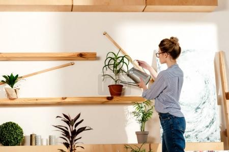 side view of young stylish woman in eyeglasses watering potted plant