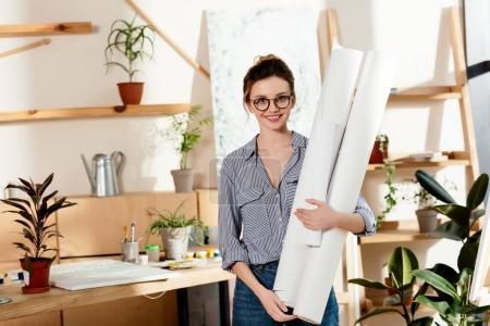 portrait of smiling stylish female artist in eyeglasses holding canvases