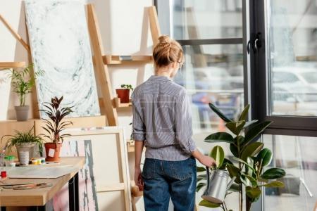 Photo pour Vue arrière du jeune artiste féminine arrosage plante en studio en pot - image libre de droit