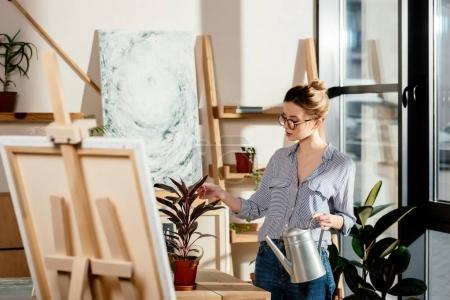 Photo pour Attrayant artiste féminine élégante dans les lunettes tenant arrosoir et touchante plante - image libre de droit