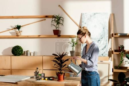 side view of stylish woman in eyeglasses watering potted plan