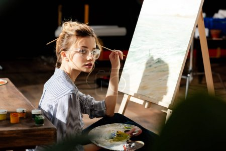 Photo for Young stylish female artist in eyeglasses holding palette and paintbrush - Royalty Free Image
