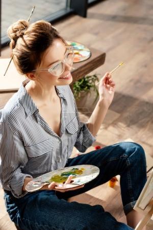 smiling stylish female artist in eyeglasses holding palette and paintbrush